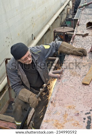 Welder on a black  metal, after  repair  of marine  ships - stock photo