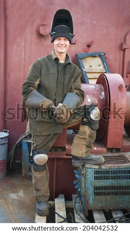 Welder on a black  metal, after  repair  of marine  ships, settlement Transforming Seashore, Russia  - stock photo