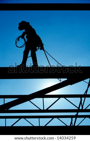 Welder walks the high steel at a construction site