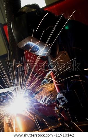 Welder welding in a factory - stock photo