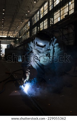 Welder welding in a workshop.