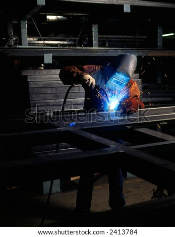 Welder welding metal in shop - stock photo