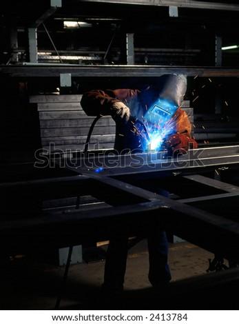 Welder welding metal in shop - stock photo
