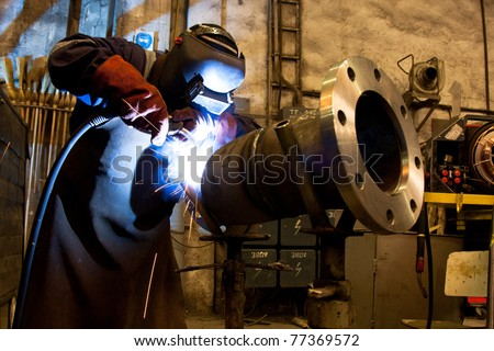 welder with protective equipment in factory - stock photo