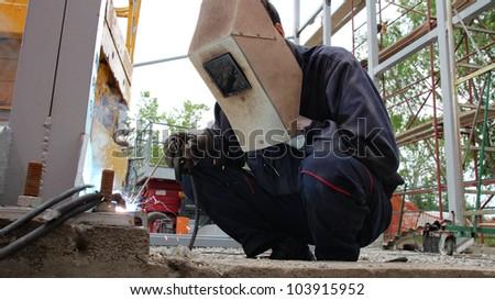 Welder with protective equipment welding outdoors. Selective focus. - stock photo
