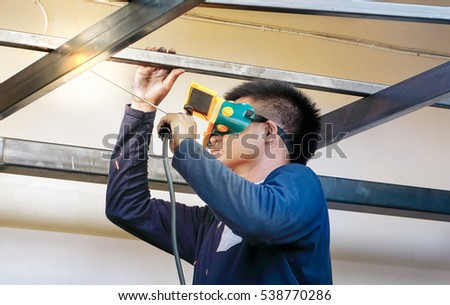 Welder with protective mask, welded roof structure