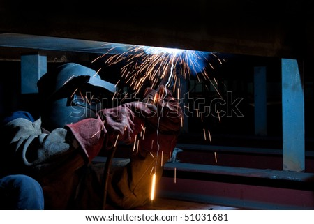 welder with protective mask welding metal and sparks - stock photo