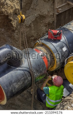welder worker cleans and grinds pipeline section ends for better welding - stock photo