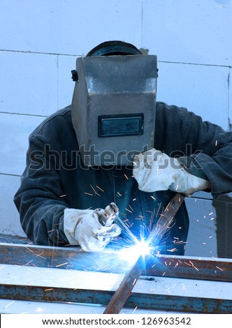 welder worker welding metal. Bright electric arc and sparks - stock photo