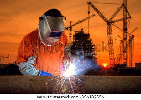 Welder working a welding metal with protective mask and sparks   - stock photo