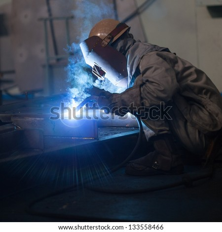 Welder working in factory - stock photo