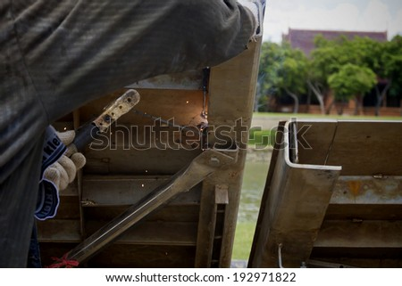 Welders in welding steel bars - stock photo