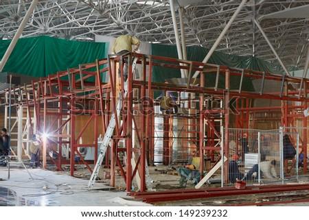 Welders weld steel frame ar construction site - stock photo