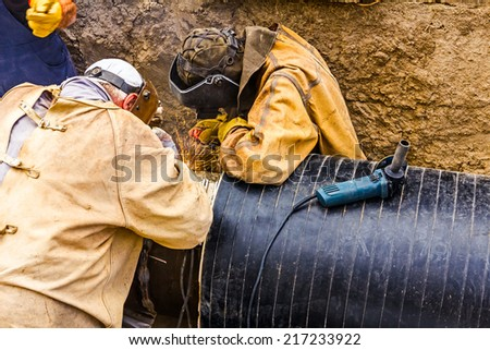 Welders welding pipeline together, teamwork - stock photo