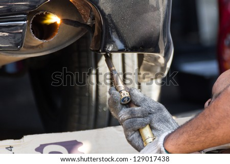 Welders were repairing  cutting exhaust pipe of a car