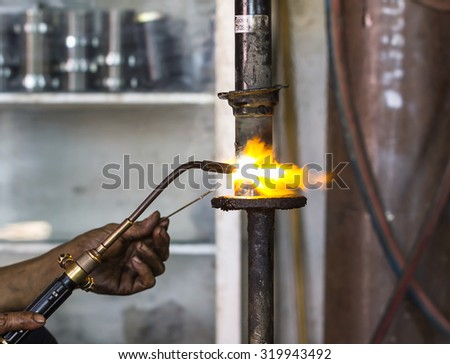 Welders were repairing cutting Shock absorbers of a car in workshop - stock photo