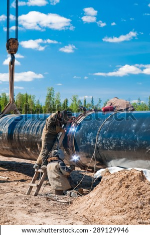 Welders working together on a difficult metal work project. Gas(oil) pipeline.