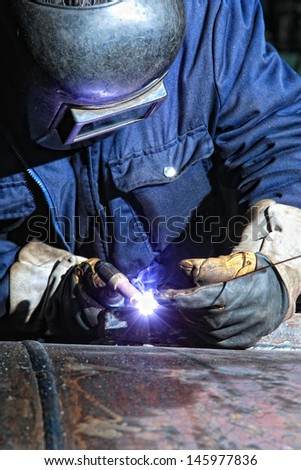 Welding and bright sparks. Hard job - stock photo