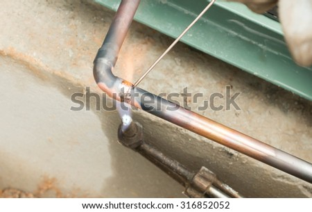 Welding copper pipes - stock photo