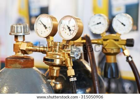 welding equipment acetylene gas cylinder tank with gauge regulators manometers - stock photo
