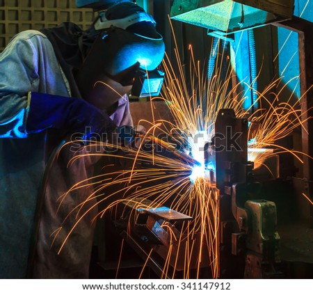 welding man Industrial automotive part in factory - stock photo