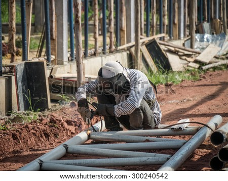 welding metal pipe together to be roof skeleton. - stock photo