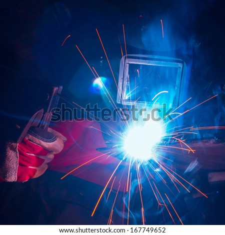 Welding metal with sparks - stock photo