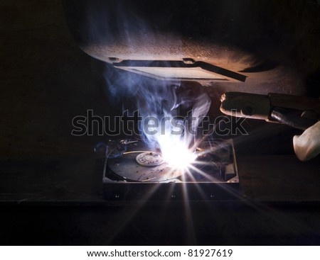 welding on a hard drive with a electrode. Nice light at the welding shield - stock photo