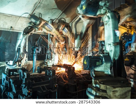 Welding robots represent the movement in the automotive parts industry - stock photo