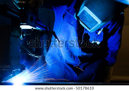 Welding sheet metal into tubes in an engineering workshop - stock photo