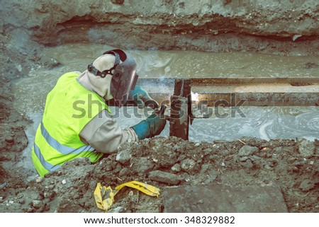 Welding steel beams in trench filled with water at construction site. Made with vintage style.