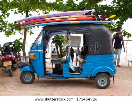 WELIGAMA, SRI LANKA - MARCH 7, 2014: Blue tuk tuk vehicle transporting surfboards on the roof. Tourism and fishing are two main business in this town.