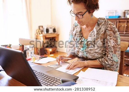 Well aged female bookkeeper busy crunching numbers on her calculator at her desk in her home office - stock photo