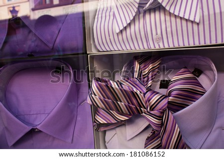 Well arranged boutique display window with a male shirts and a tie