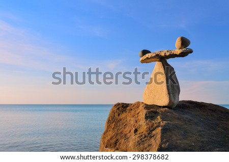 Well-balanced of pebbles on the top of boulder - stock photo