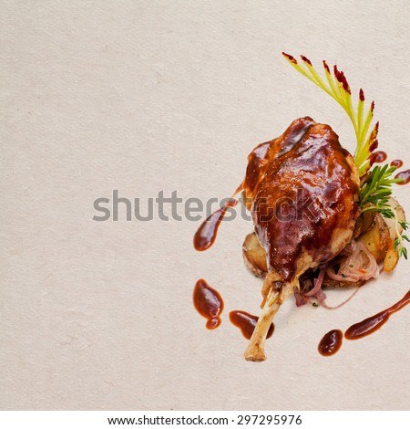 Well-browned and crisp duck confit.  French dish made with the leg of the duck. Roasted duck leg with potatoes and brown garlic bacon sauce, seasoned herbs. Aged paper background. Copy space.  - stock photo