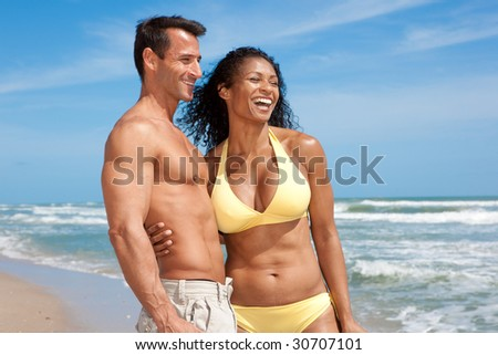 Well build couple standing at the beach, having fun - stock photo