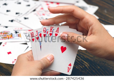 Well-conditioned female hands holding playing cards with poker strongest combination - royal flush - stock photo