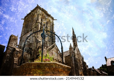 Well decorated with flowers at the square in front of Saint Ronan church in  medieval village Locronan. Brittany, France. Retro aged photo with scratches. - stock photo