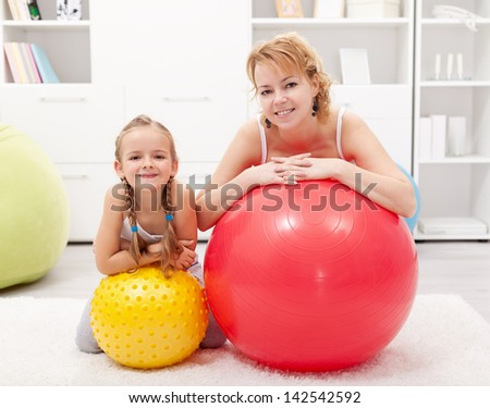 Well deserved relaxing after exercise - woman with little girl and large gymnastic balls