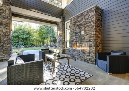 Well Designed Covered Patio Boasts Stone Fireplace, Wicker Patio Chairs  Facing Gorgeous Rustic Wood Coffee