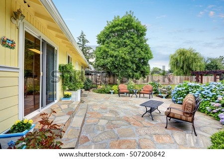 Awesome Well Designed Patio Area With Stone Floor In The Backyard Of A Yellow  House. Relaxing
