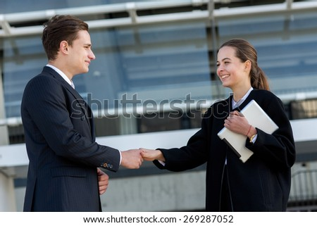 Well done business deal. Portrait of two confident and motivated partners. Man and woman are shaking hands, both have agreement on essential business project. Outdoor business concept