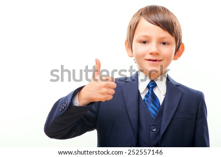 Well done. Closeup portrait of a business child wearing suit and tie showing OK sign while standing isolated on white background - stock photo