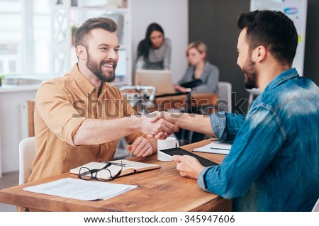 Well done! Two confident young men shaking hands and smiling while sitting at the desk in office with two people working in the background  - stock photo