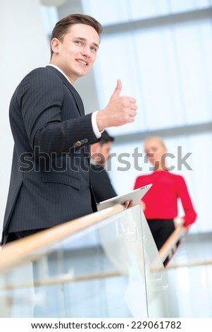 Well done. Young handsome businessman is smiling and showing OK, while standing with tablet. Two his colleagues are standing on the background and discussing important business stuff. - stock photo