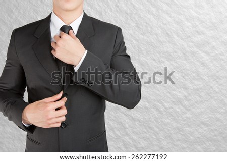 Well dressed businessman looklike smart adjusting  his neck tie on color background : fill text - stock photo