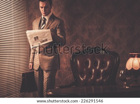Well-dressed businessman reading newspaper - stock photo
