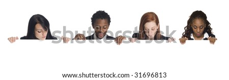 Well dressed businesspeople looking down over the edge of a blank sign they are holding. - stock photo
