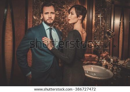 Well-dressed couple in luxury bathroom interior. - stock photo